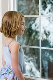Snow Day. A young child looking out the window with wonder at the snow Stock Photo
