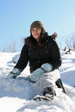 Snow Day. A teenage girl sitting in the snow on a hill Royalty Free Stock Photography