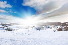 Snow declivities. On background bright sky with solar glow. Composition of the nature Stock Images