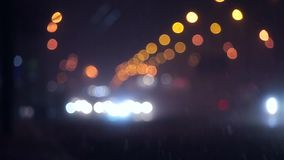 Snow defocused night traffic in city. Snow down defocused downtown night traffic in city stock footage