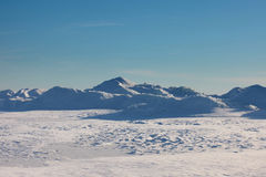 Snow desert and blue winter sky. Mountains on the horizon Stock Image