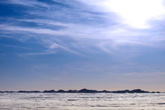 Snow desert and blue winter sky. Mountains on the horizon Royalty Free Stock Photo
