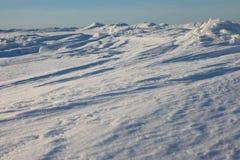 Snow desert and blue winter sky. Mountains on the horizon Stock Photos