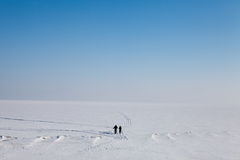 Snow desert. The boy and girl walking on snow-covered ice of the river Volga Stock Images