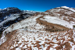 Snow Dirt Road Mountain Pass. Winter snow landscape at Sani Pass in the Southern Drakensberg mountains.A popular hiking and climbing area in the seasons. This Stock Photo