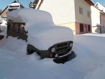 The Snow-downed olive-green car parked beside the house Stock Photos