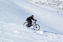 Snow downhill on bike Royalty Free Stock Photo