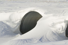 Snow drift over a culvert. A snow drift over a galvanized metal culvert Stock Image