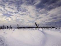 Snow Drift At Sunset Fence Line. Snow Drift blue sky winter farm field Fence Line Royalty Free Stock Image