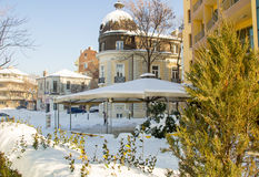 Snow drifts on green bushes and summer café in the center of the old town of Pomorie, Bulgaria Royalty Free Stock Photography