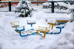 Snow drifts and debris on the playground in one of the cities of Russia in the winter stock image