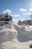 Snow Drifts on a Street After a Snow Storm. Snow drifts on a street before the snow plow came, interesting sculpture shapes with houses in the background Stock Photo