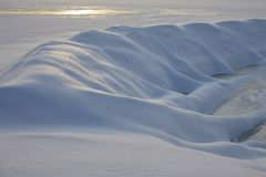 Snowdrift in the form of a snake that crawls under the ground. sunny day winter stock photos