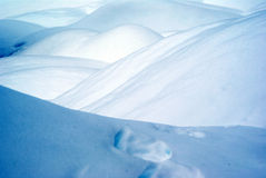 Snow dunes and footsteps on a winter morning in Royalty Free Stock Photos