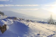 Snow dunes with paladoken mountains background in Erzurum, Turkey. With mist stock image
