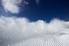 Snow dust cloud after skier on the ski slope Royalty Free Stock Images