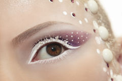 Snow eye makeup. Snow eye makeup with white eyelashes and purple shadows with dots and rhinestones on the face stock image