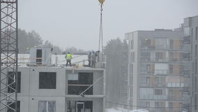Snow fall and construction site workers build house in winter stock footage