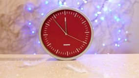 Snow fall on a New Year clock with luminous blue lanterns in the background. On the table are a green tinsel and christmas balls. Still life stock video footage