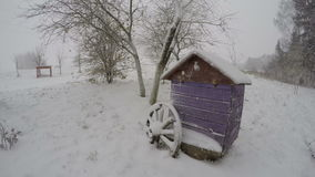 Snow falling on beehive, time lapse 4K. Snow falling on violet beehive with wooden wheel in countryside yard by the fields, time lapse 4K stock video