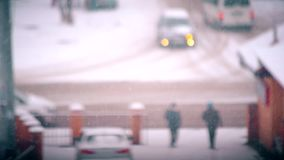 Snow falling on blurred city road landscape background. With cars driving by and people passing by stock footage