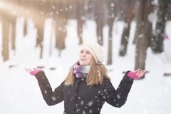 Snow falling and cute young girl feeling happy outdoors. Winter royalty free stock photography