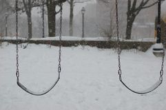 Snow falling on empty swings in a deserted park. It is cold and eerie and dingy. A cold winters day, Snow is falling and the park is empty. The scene is cold Royalty Free Stock Image