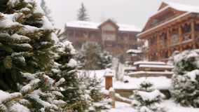 Snow falling fir tree branches, wooden cottages on background. Heavy snowfall at mountain village ski resort. Cold. Frosty winter day in the mountains stock video footage