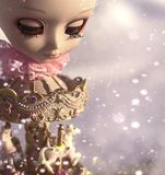 Snow falling on the gold carousel with a dollish head on it royalty free stock images
