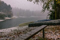 Snow falling on lake boats. Canoes and boats near bench left over from summer near lake covered in snow Stock Image