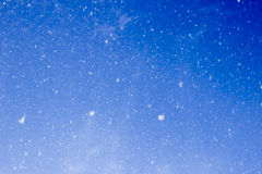 Snow falling. In motion, white dots - snowflakes on blue sky background Royalty Free Stock Photography