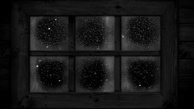 Snow falling outside window at night
