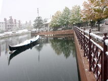 Snow falling into pond with boat Royalty Free Stock Images