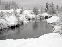 Snow falling on a river with snowy banks in Whistl. Er British Columbia Stock Image