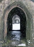 Snow falling in the ruins of heptonstall church doorway Stock Photo
