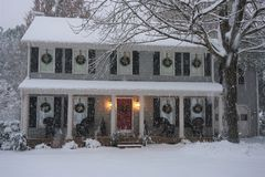 Snow falling on a suburban home decorated for Christmas royalty free stock photo