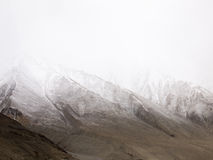 Snow falling on top of mountains Stock Photo