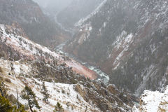 Snow Falling in Valley With Rich Red Earth. Snow falling and littering the red earth ground as a river permits water to cascade to lower ground Stock Image