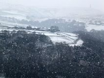 Snow falling in a yorkshire dales landscape with winter trees stock photo