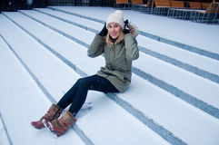 Snow falling. Young woman sitting on the stairs and watching snow falling Stock Photo