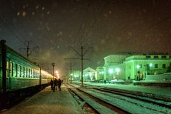 The snow falls in the light of the station lights. stock images