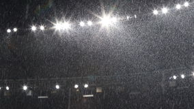 Snow falls over stadium lights stock video