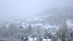 Snow falls on small village at foot of wooded hill stock video