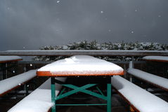 Snow falls on a table and beerbanks in a terrace. Snow falls on tables and banks in a terrace during a cold spell on Herzogstand mountain in the bavarian alps Stock Images