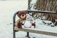 Snow falls on the toys sitting on the bench. Royalty Free Stock Photos