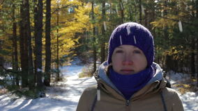 Snow falls from the trees onto the head of the girl in the winter forest. On a sunny day. Close-up stock video footage