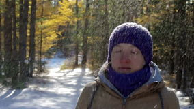 Snow falls from the trees onto the head of the girl in the winter forest. On a sunny day, eyes closed. Close-up stock video footage