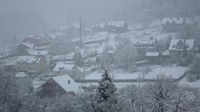 Snow falls on village at foot wooded hill. Slow motion stock footage