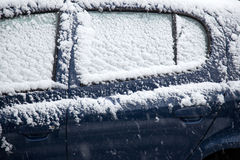 Snow fals on door of blue car Royalty Free Stock Images