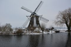 Snow in February. In the Netherlands, dutch mill, provincie Utrecht, the name of the river is Gein in Abcoude Royalty Free Stock Photo
